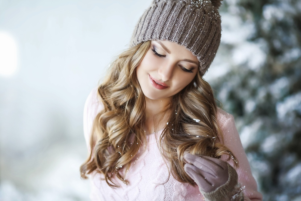 girl looking at her hair in a hat in the winter